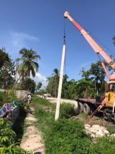 crane lifts post into hole